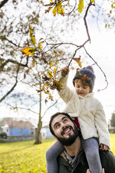 Little girl on shoulders of her father in autumnal park - MGOF03207