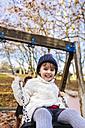Portrait of happy little girl on a swing - MGOF03210