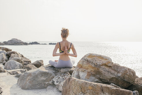 Woman sitting in lotus seat, meditating on the beach - MOMF00057