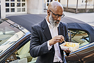Mature businessman eating French fries - FMKF03821