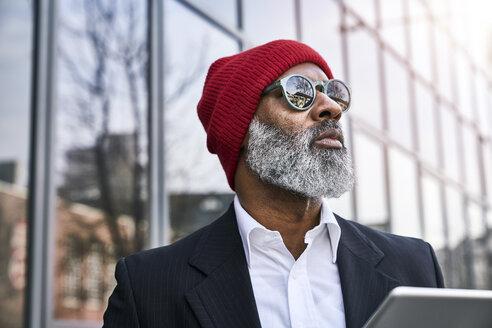 Mature businessman using digital tablet in the street - FMKF03830