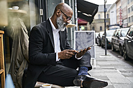 Mature businessman sitting in cafe using digital tablet - FMKF03851