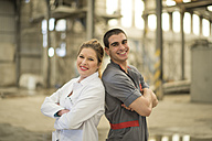 Colleagues in factory standing back to back, smiling - JASF01576