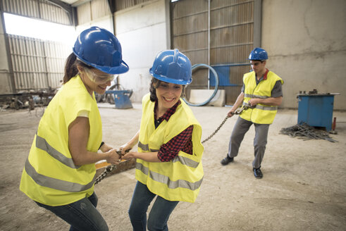 Female skilled workers in concrete factory pulling machine part - JASF01591