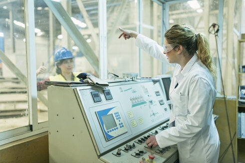 Female colleagues working at control panel in a factory - JASF01597