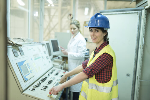 Female colleagues working at control panel in a factory - JASF01600