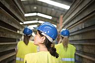 Three industry workers standing by steel girders, looking up - JASF01618