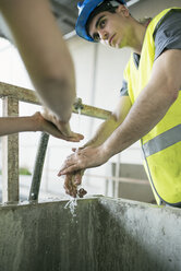 Workers in factory washing their hands - JASF01624