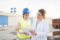 Female colleagues doing measurments in a factory, using digital tablet - JASF01639
