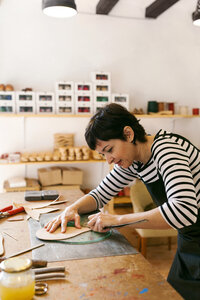 Shoemaker working on template in her workshop - VABF01307