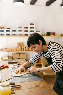 Shoemaker working on template in her workshop - VABF01307