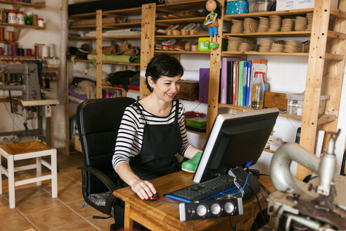 Smiling shoemaker using computer in her workshop - VABF01316