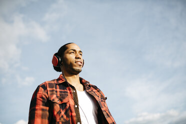 Portrait of young man listening music with headphones in front of sky - JRFF01290