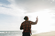 Back view of man walking on the beach listening music with headphones - JRFF01293