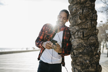 Spain, smiling young man with headphones leaning against palm tree trunk looking at cell phone - JRFF01296
