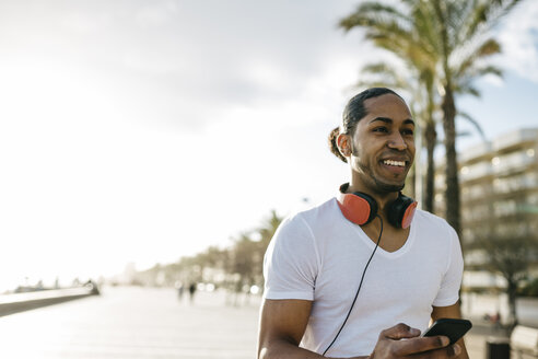 Spain, portrait of smiling young man with headphones and cell phone on beach promenade - JRFF01299
