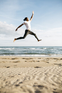 Young man jumping in the air on the beach - JRFF01302