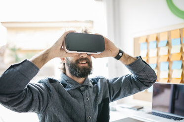 Man wearing Virtual Reality Glasses working on new project in his office - JRFF01310