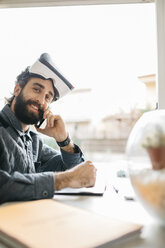 Portrait of smiling man with Virtual Reality Glasses on the phone in his office - JRFF01313