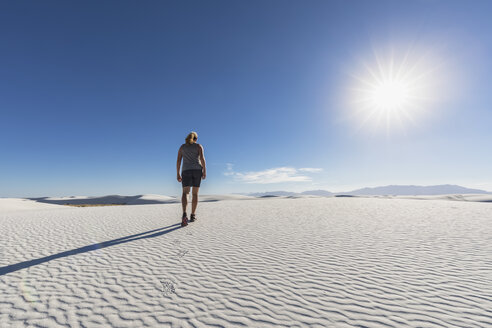 USA, New Mexico, Chihuahua Desert, White Sands National Monument, woman hiking on dune - FOF09214