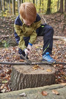 Redheaded boy treating branch with bow in autumnal forest - JEDF00285