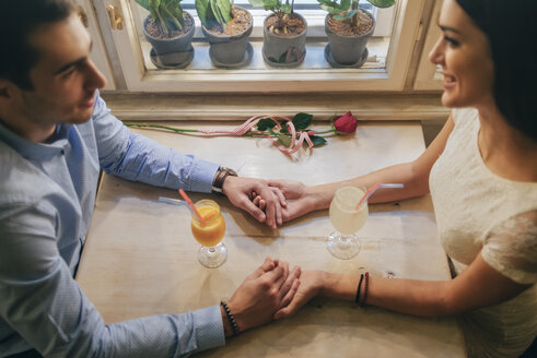 Couple in love holding hands in a restaurant - MOMF00078