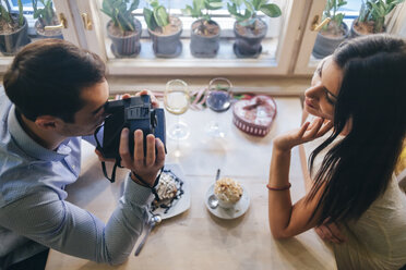Young couple taking instant photos, top view - MOMF00084