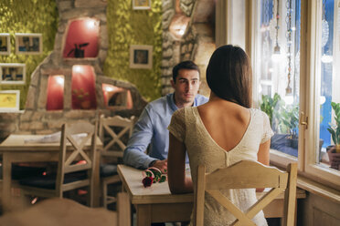 Back view of young woman sitting face to face with her boyfriend at table in a restaurant - MOMF00090