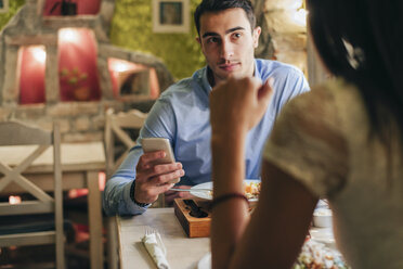 Man with cell phone face to face with his girlfriend in a restaurant - MOMF00108