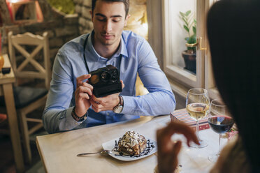 Man taking instant photos of his girlfriend - MOMF00111