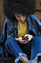 Young woman wearing jeans and jeans jacket using cell phone - KKAF00696