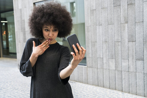 Portrait of young woman taking selfie with smartphone - KKAF00705