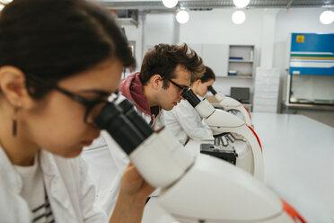 Laboratory technicians using microscopes in lab - ZEDF00576