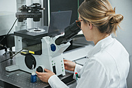 Laboratory technician using microscope in lab - ZEDF00579