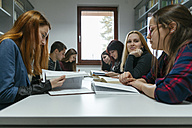 Group of students learning together in a library - ZEDF00590