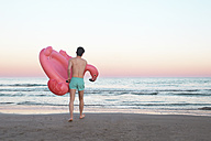Back view of young man with inflatable pink flamingo on the beach - RTBF00816