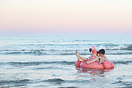 Couple in love floating with inflatable pink flamingo on the sea at sunset - RTBF00819