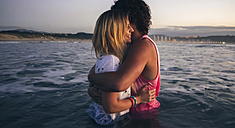 Young couple hugging in the sea at dusk - DAPF00685