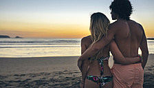 Young couple watching the sunset on the beach - DAPF00688
