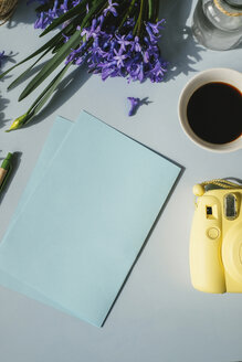 Sheets of paper, camera, cup of coffee and spring flowers on light blue background - MOMF00133