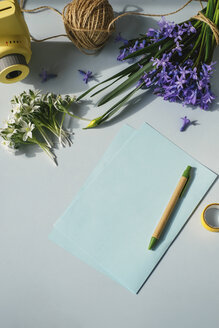 Sheet of papers, camera and spring flowers on light blue background - MOMF00136
