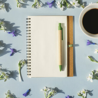 Notebook, pen, cup of coffee and spring flowers on light blue background - MOMF00139