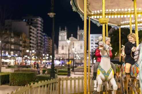 Two girls riding a Christmas carousel - MGOF03213
