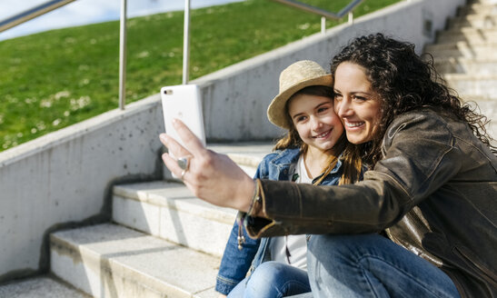 Happy mother and daughter taking a selfie on stairs - MGOF03217