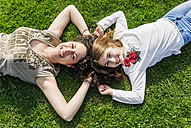 Mother and daughter having fun lying in the grass - MGOF03220