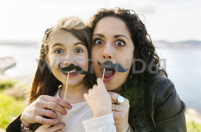Mother and daughter having fun holding fake moustaches - MGOF03232