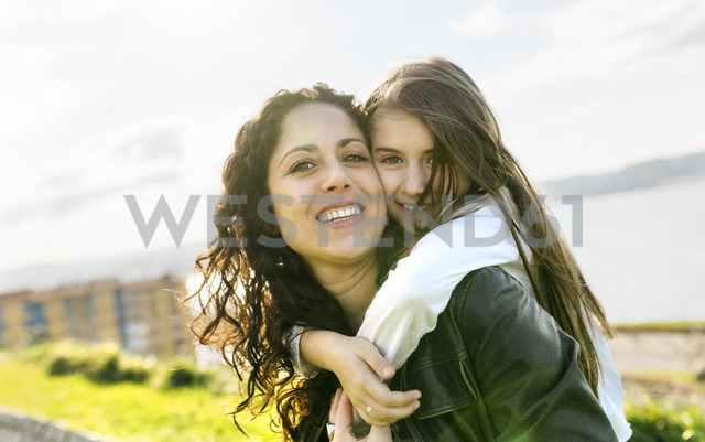 Portrait of happy mother carrying daughter outdoors - MGOF03235