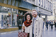 Portrait of happy couple shopping in the city - MOMF00144