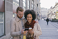 Couple in the city with cell phone and shopping bags - MOMF00150