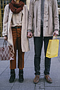 Couple with shopping bags holding hands - MOMF00156